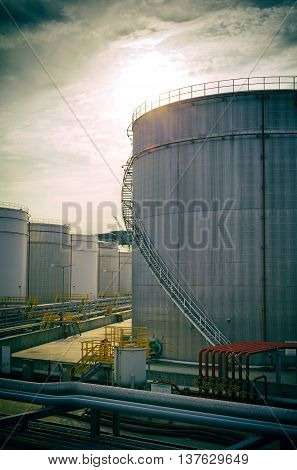 Capacities and a petroline on a tank farm stylisation under a film photo.