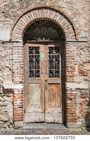 Old wooden door with upper railing and brick archway.