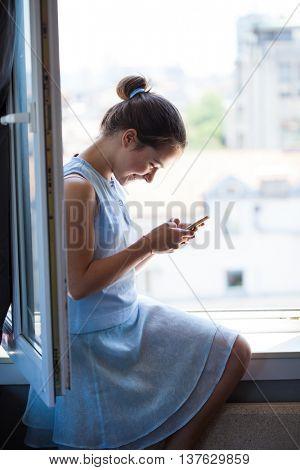 happy teen girl with smart phone sit on window