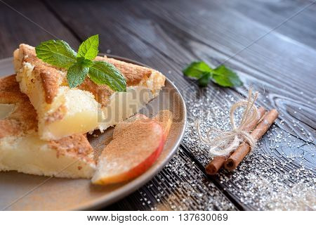 Pear pie sprinkled with cinnamon on a wooden background