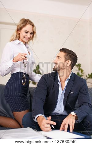 Secretary holding handcuffs to boss in office seduction
