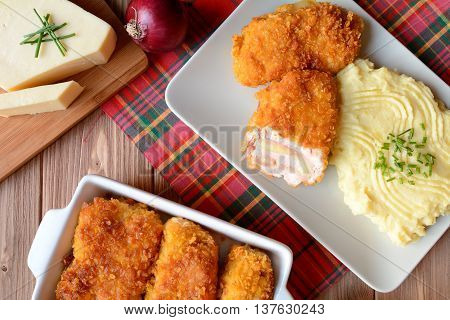 Traditional Cordon bleu with mashed potatoes on a wooden background