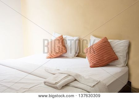 white pillow and orange pillow on bed and with blanket in vintage bedroom with lighting in morning
