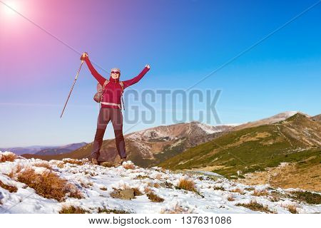 Happy Female Hiker with Backpack and walking Poles makes Success gesture raising Hands up european Mountains Scenery View and Sun shining from blue Sky