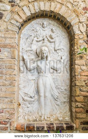 Bas relief surrounded by brick wall representing the Virgin Mary surrounded by angels.