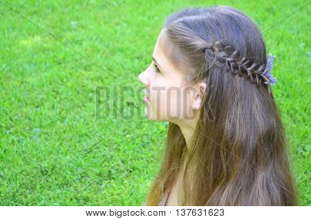 Hairstyle with long hair - a girl on a background of green grass