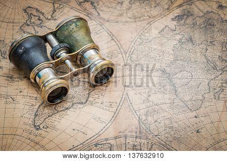 Pair of old binoculars on a vintage map
