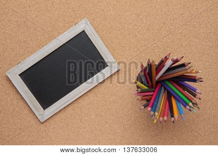 blackboard with wooden frame and colored pencils on cork background