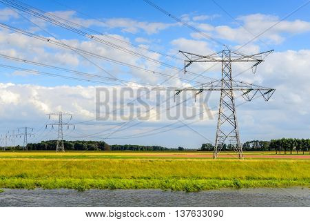 High voltage lines and power pylons in a colorful Dutch polder. In the foreground is a small creek.
