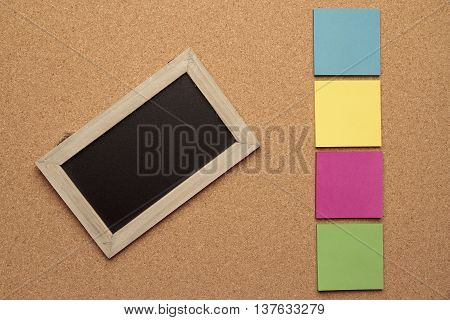 blackboard with wooden frame and four colored notes on cork background