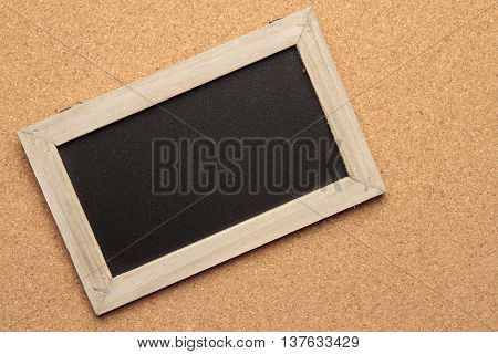 blackboard with wooden frame on cork background