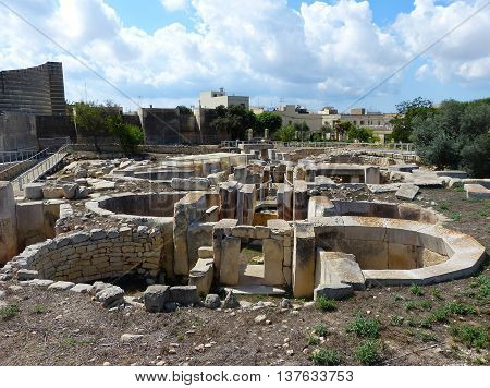 Tarxien, Malta - September 23, 2013. Megalithic structures of the Tarxien Temples with neolithic megaliths, walkways and residential buildigs in the background.