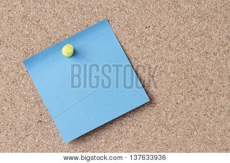 blue note on a cork board with a yellow push pin