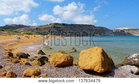 Ramla Bay, Malta - September 27, 2013. Ramla Bay - the biggest sandy beach on Gozo, with large stones on the foreground, and people on the beach.