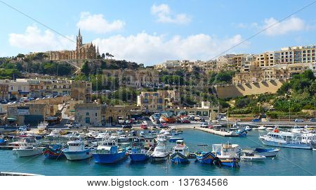 Mgarr, Malta - September 27, 2013. View over Mgarr harbour on Gozo island, with residential and commercial buildings, church on top of the hill and boats.
