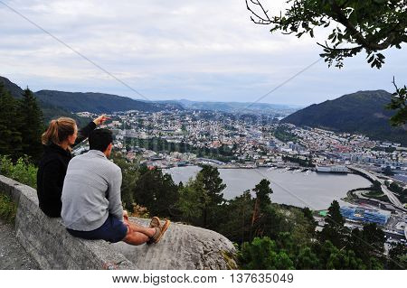 BERGEN, NORWAY - AUGUST 10, 2014: Young woman point at Bergen city from viewpoint of Floyen hill in Bergen, Norway. Bergen is one of the major tourist destinations of Norway.
