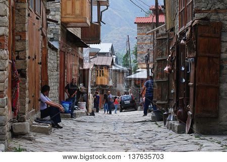 Lahic, Azerbaijan - August 30, 2014. Street view on unevenly paved Huseynov street, the main street of Lahic mountainous village of Azerbaijan, with smooth pale river stones, coppersmith workshops and people. Houses with wooden box balconies are built tra