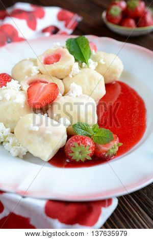 Sweet boiled dumplings filled with strawberries with a curd and a strawberry sauce