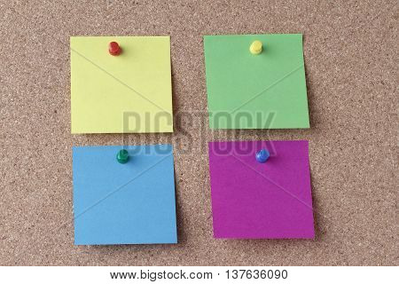 four colored notes with colored push pins on a cork board