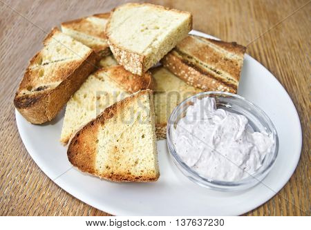 greek bread with olive oil and yoghurt sauce on wooden table