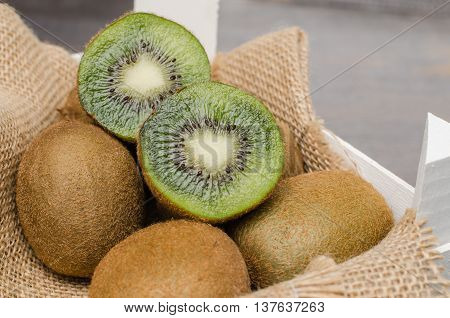 Box of fresh kiwi in on wooden background