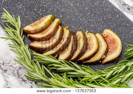 Fresh sliced figs and rosemary on cutting board