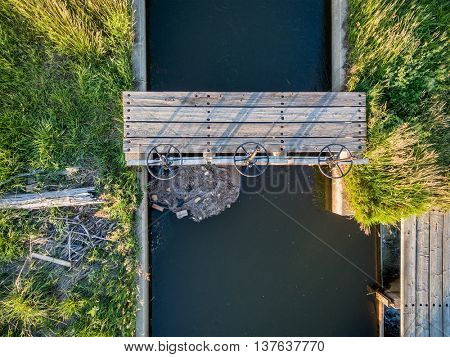 aerial view of irrigation ditch with gates and footbridge in Colorado