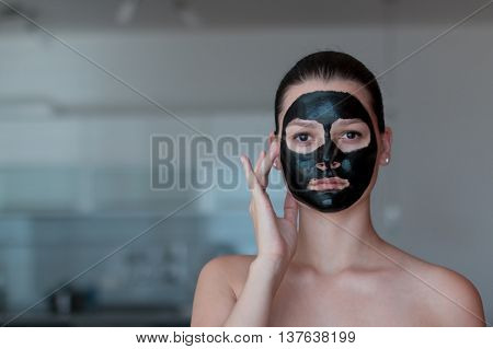 Young beautiful woman with a black mask for the face in the bathroom