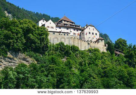 Vaduz, Liechtenstein - June 30, 2015. Schloss Vaduz castle looms over the capital of Liechtenstein from the hill above.