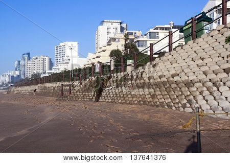 Concrete Retaining Wall  On Empty  Beach  Against City Skyline