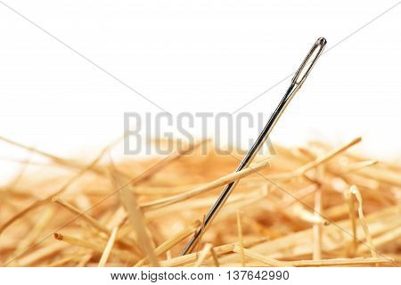 Closeup of a needle in haystack. Isolated on white background