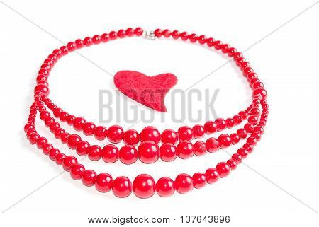 Red beads with a red heart in the middle (on a white background) selective focus on the front beads