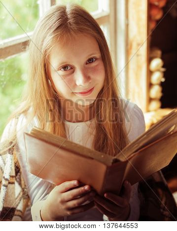 Young beautiful girl reading a book by the window.