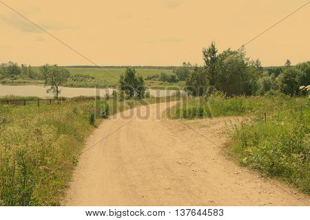Rural landscape with a lane to the river going across the field (vintage style subdued colors)