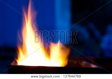Blurred silhouettes of flames of fire in the evening (as an abstract background) with copy space on the right for your text