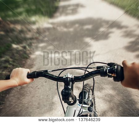 Handlebar with child hands close up image