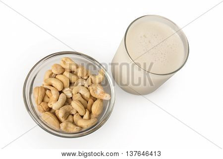 A glass of cashew milk with a bowl of cashews next to it.