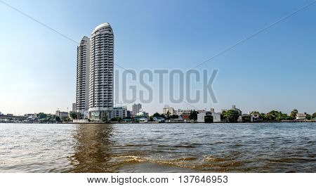 Cityscape with modern building near the river in the afternoon at Chao Phraya River in Bangkok Thailand