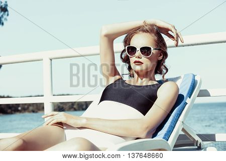 Young girl model in sunglasses and elegant black and white sexy swimsuit lingerie near swimming pool with clear blue water, . Full relax. Vintage. Sunbathe.