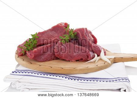 Chopped raw fresh beef pieces on wooden kitchen board isolated on white background. Culinary meat eating.