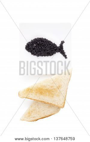 Delicious black caviar in fish shape and toast isolated on white background. Exquisite luxurious gourmet eating.