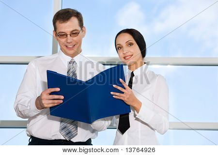 Portrait of businessman reading documents with his colleagues in the building with glassy walls