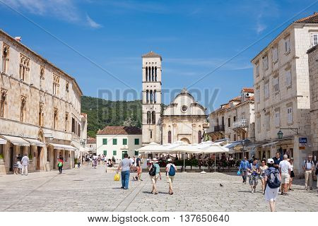 HVAR CROATIA - JUNE 20 2014: Tourists at Hvar town main square in front of the St Stephen Cathedral in Hvar Croatia