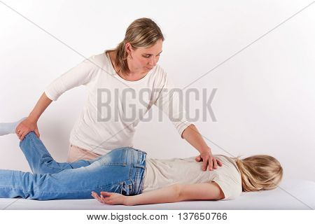 Young girl receives Bowen therapy similar to back massage. Bowen therapy is a holistic system of healing.