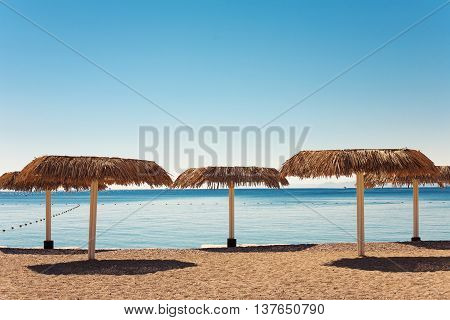 Empty beach with straw umbrellas in Eilat city Israel