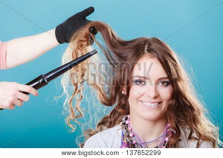 Hairdresser curling woman hair with electric iron curler. Hairstylist making girl hairstyle. Attractive pretty young female.