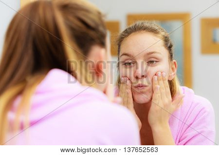 Woman Cleaning Her Face With Scrub In Bathroom.