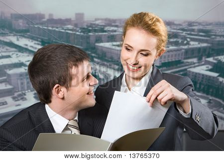 Businessman holding the grey paper case looking to the businesswoman taking document from the case and gray winter city on the background