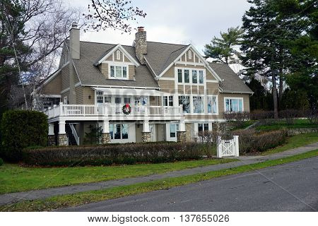 HARBOR SPRINGS, MICHIGAN / UNITED STATES - DECEMBER 25, 2015: A large mansion with a balcony on East Bluff Drive in Harbor Springs, Michigan, with a view of Little Traverse Bay.