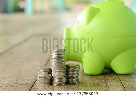Pig bank and coin on a wooden floor